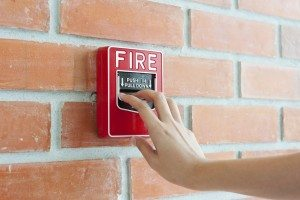 Hand pulling down fire alarm
